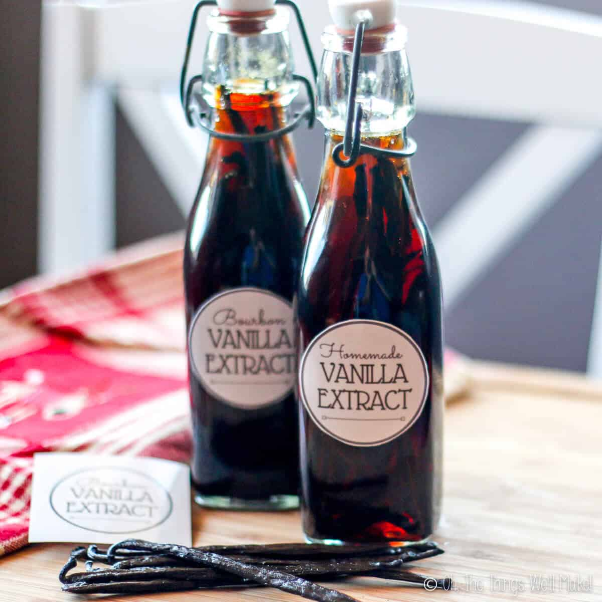 Close-up of two bottles filled with homemade vanilla extract, with fresh vanilla beans next to them.