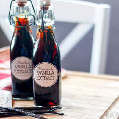 Two bottles of homemade vanilla extract with vanilla beans next to them.