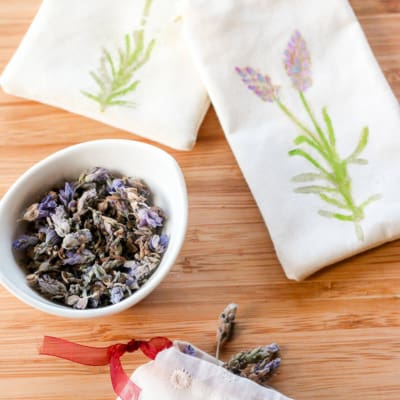 A cup of lavender next to two homemade cream colored lavender sachets with lavender print on them.