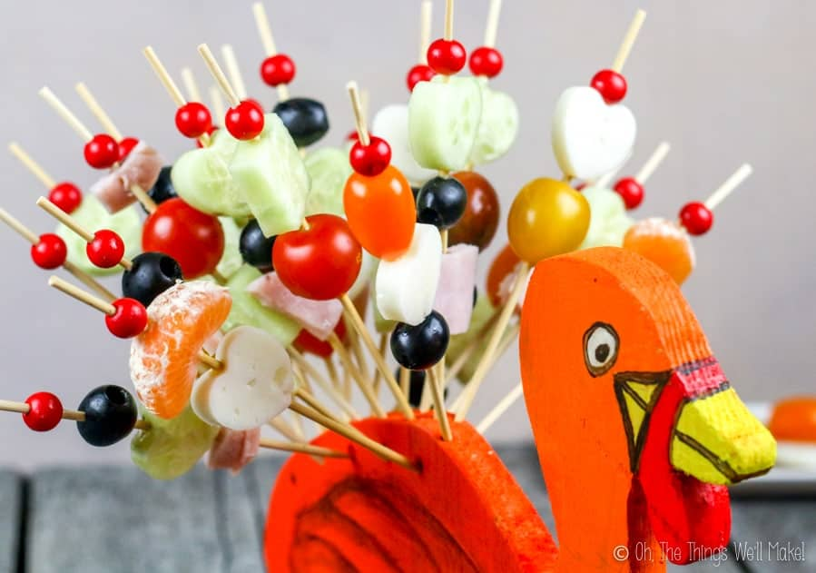 Closeup of skewers filled with fruits, vegetables, ham and cheese on a stand shaped like a turkey