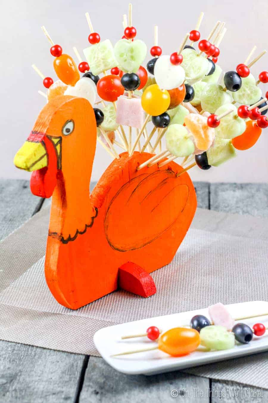 A turkey-shaped display holder with skewers filled with fruits, vegetables, ham, and cheese