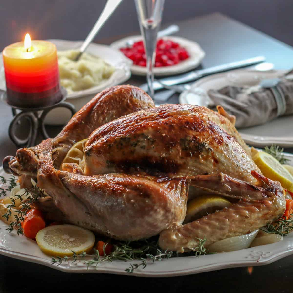 A roasted turkey on a platter garnished with lemon slices, thyme, and roasted vegetables.