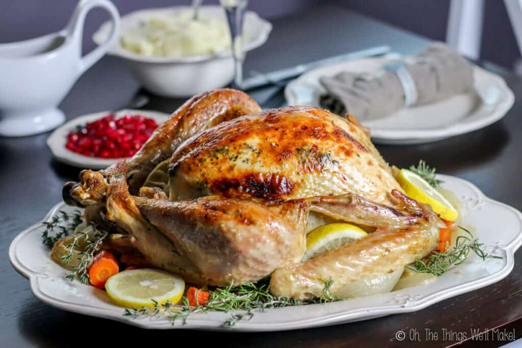 A roasted whole turkey on a platter, garnished with vegetables, lemon slices, and herbs.