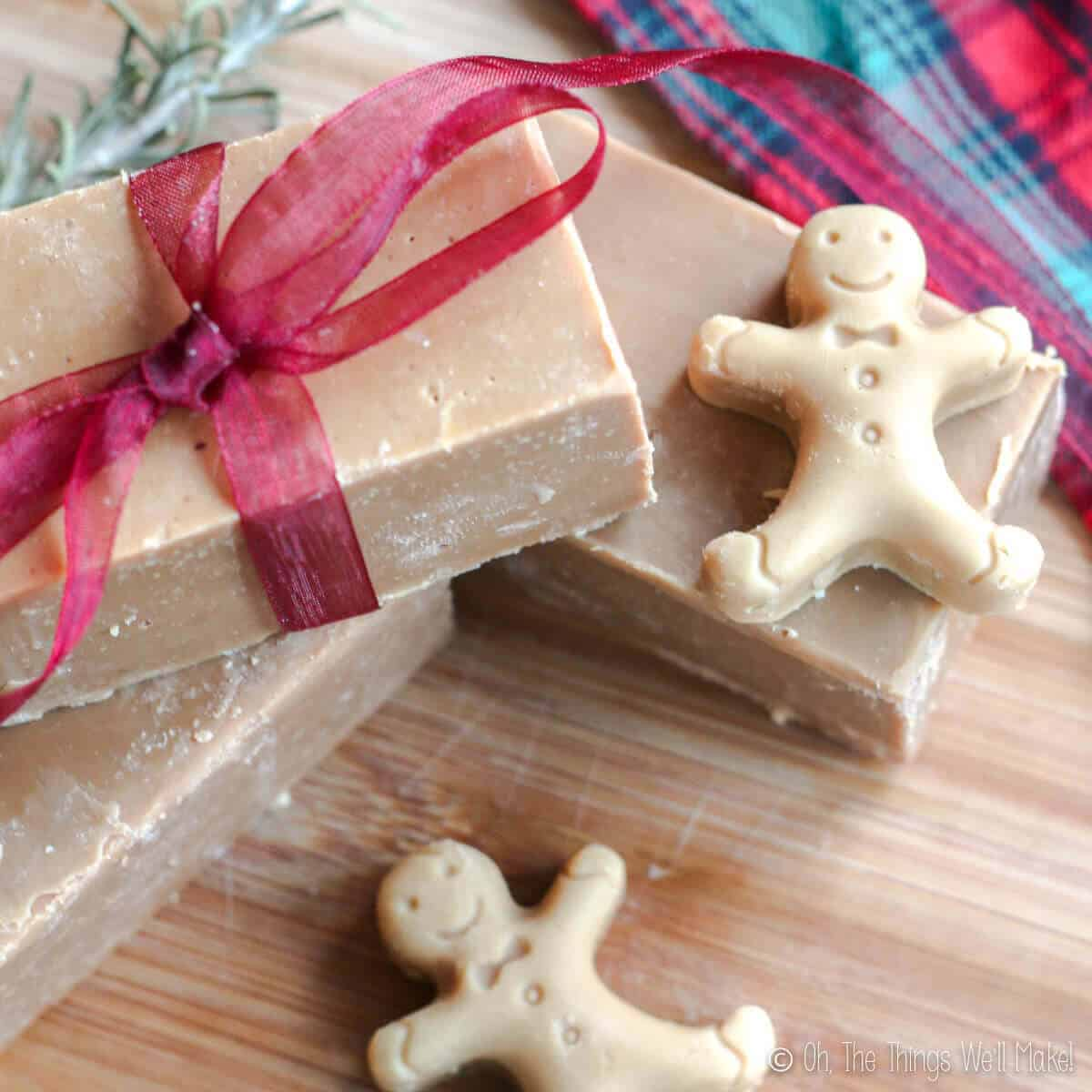 Overhead view of 3 bars of homemade gingerbread soap with some mini gingerbread man shaped soaps