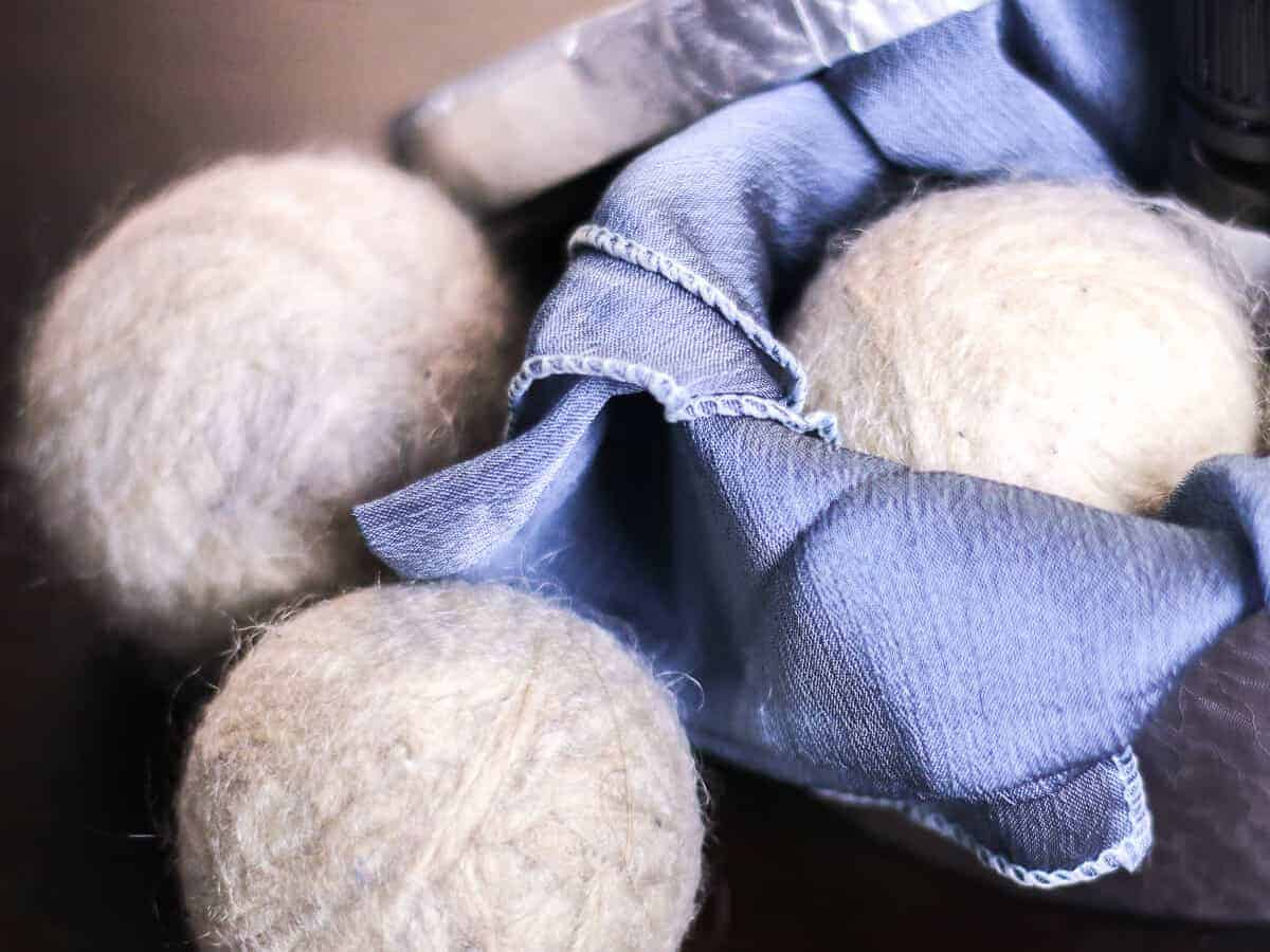 Close-up of homemade wool dryer balls. One dryer ball place in a blue fabric basket.