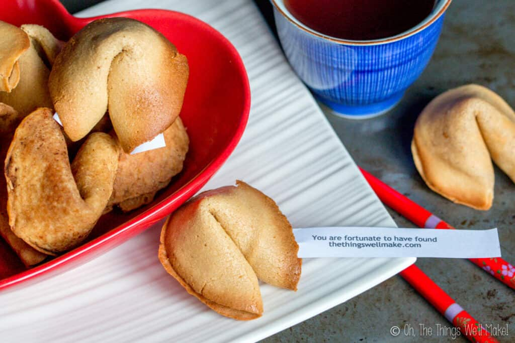 "Overhead view of several homemade fortune cookies in a heart-shaped red bowl next to a cup of tea and a separate fortune cookie. One has a fortune that says ""You are fortunate to have found thethingswellmake.com."""