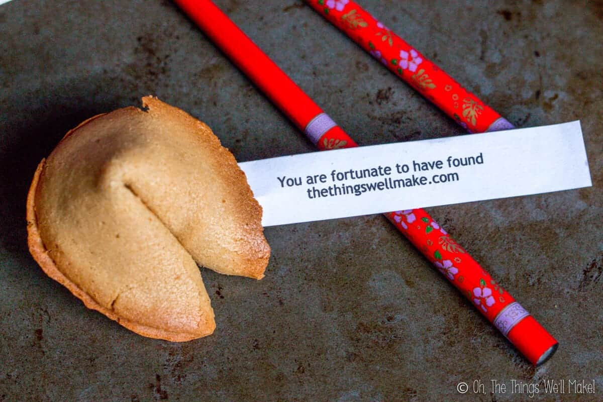 """Overhead view of a homemade fortune cookie with a fortune coming out of it that reads """"You are fortunate to have found thethingswellmake.com"""" over red chopsticks."""