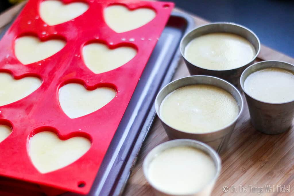 panna cotta mixture in aluminum flan molds and silicone heart shaped molds
