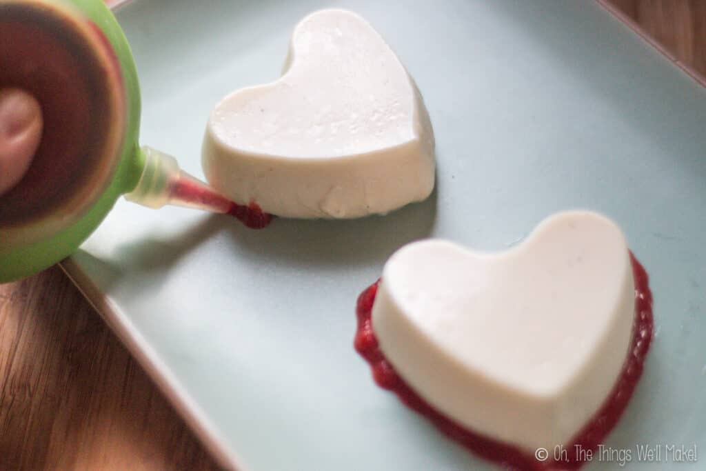 Decorating a homemade creamy panna cotta by piping a berry puree around the edges of the bottom.