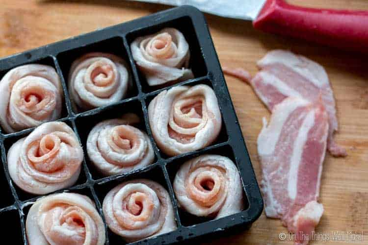 Several bacon roses have been placed into a silicone ice cube tray to hold them in place.