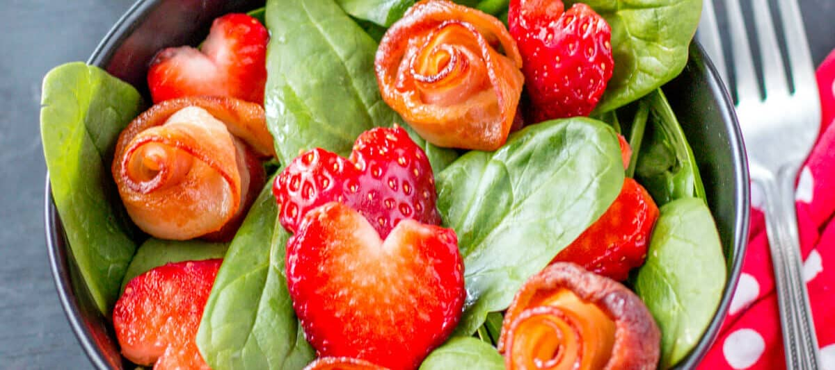 Closeup of a cute salad, perfect for Valentine's Day! It has strawberry hearts and bacon roses.