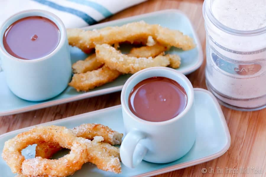 Overhead view of two plates of churros sprinkled with sugar with cups filled with Spanish hot chocolate.