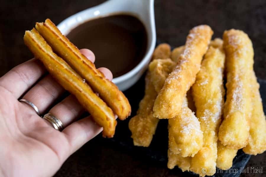2 traditional (wheat based) churros being held next to a plate of grain-free churros.
