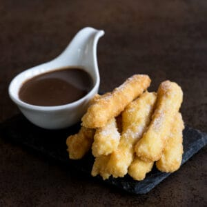 Grain-free, gluten-free churros on a slate platter accompanied by a cup of thick Spanish hot chocolate