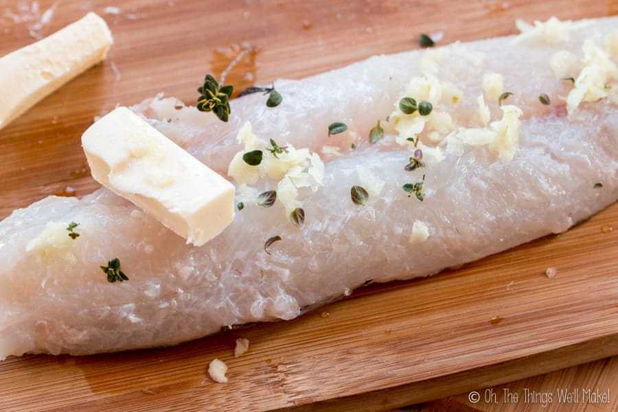 A fillet of hake of with butter, thyme, and garlic on top.