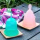 Two menstrual cups, one green Sckoon and one pink generic placed on square wooden platters with a floral bag behind them.