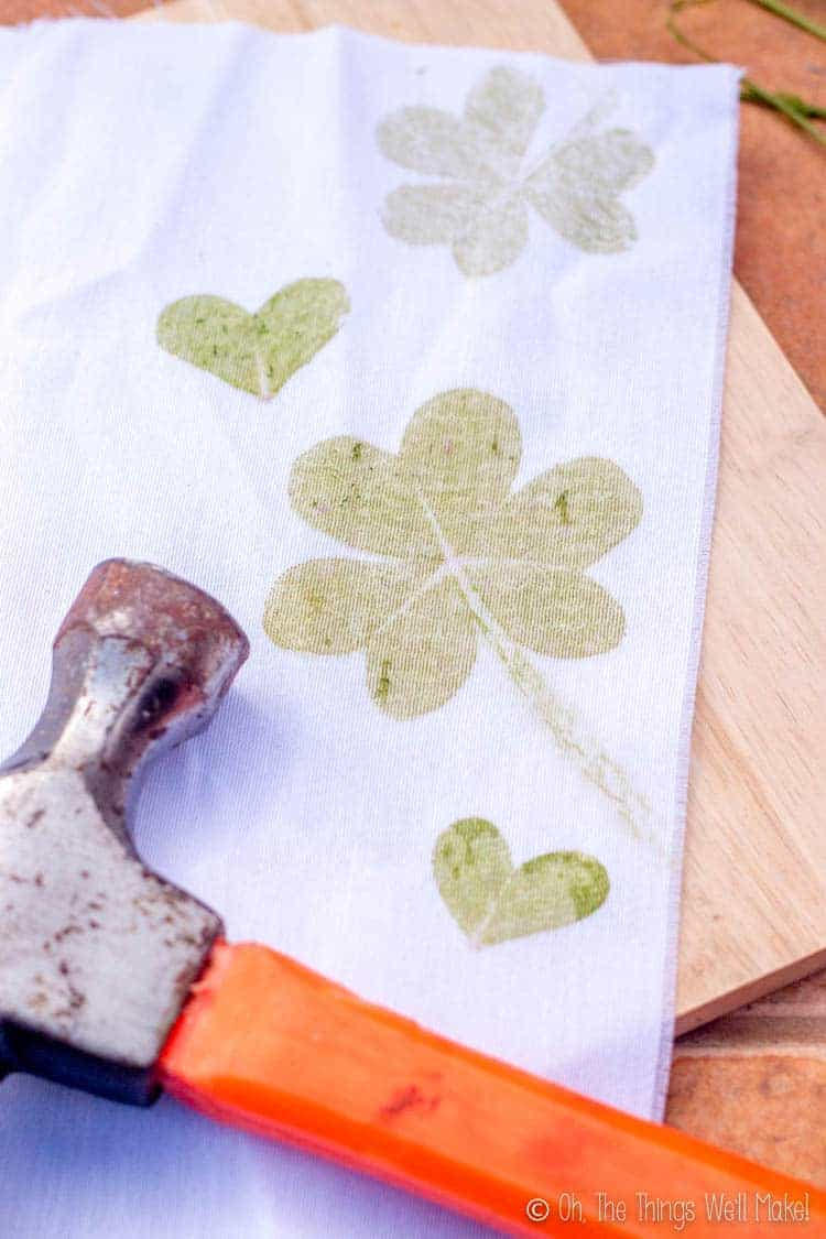 A white cloth with shamrock prints and clover heart prints.