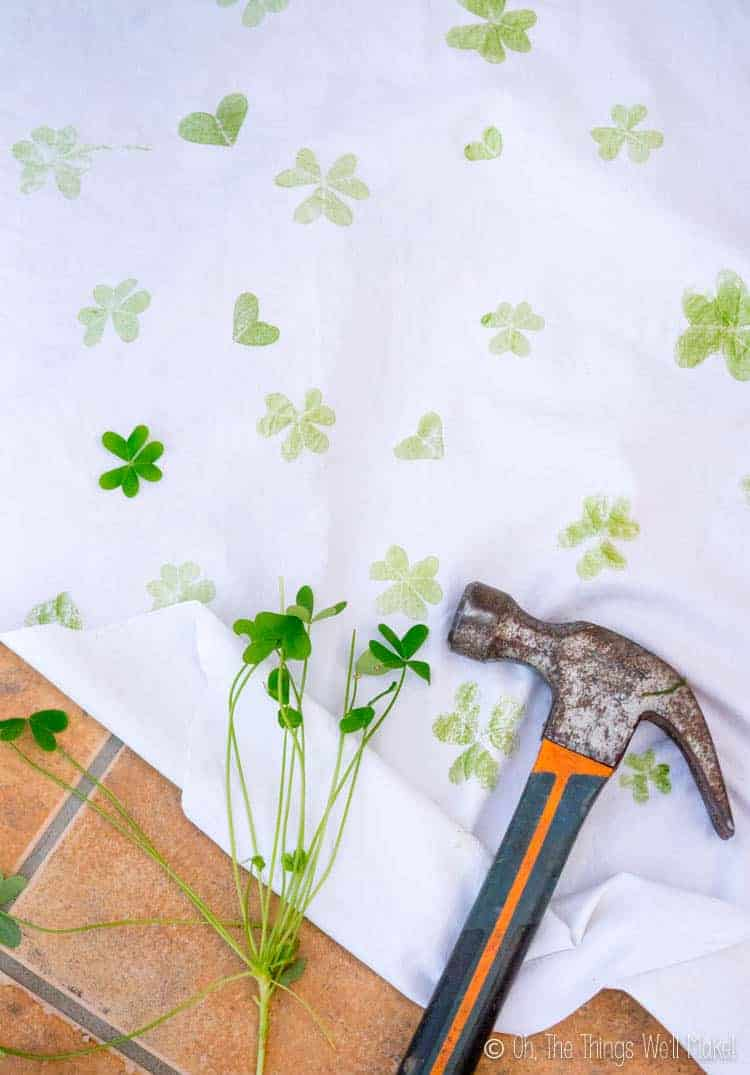 Overhead view of a hammer and clover leaves on a cloth with shamrock and clover heart prints on it.