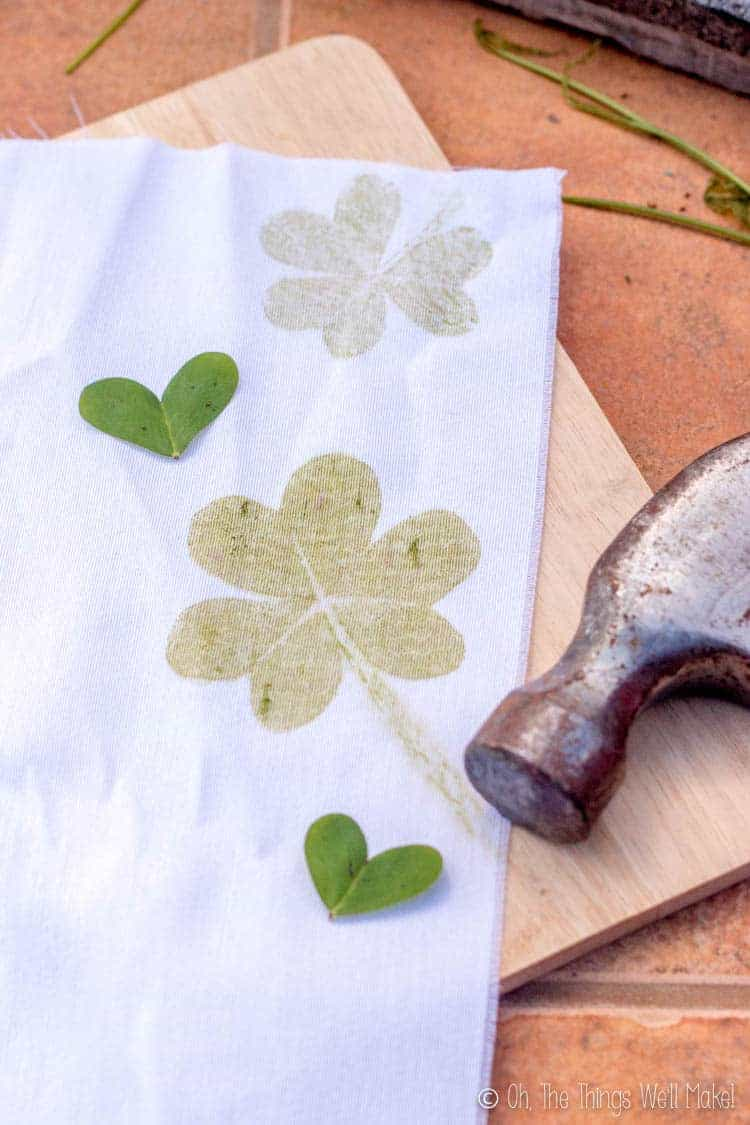 A cloth with shamrock prints and clover hearts on a wooden cutting board.