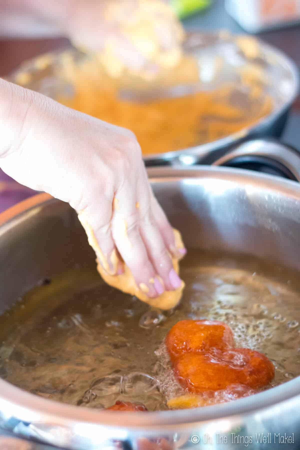 Adding pumpkin fritter batter to hot oil