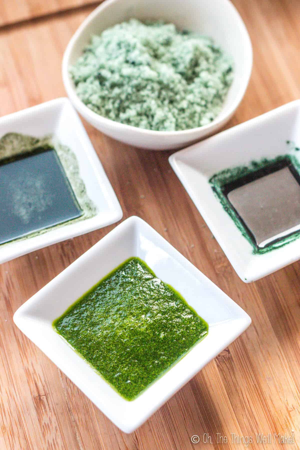 Overhead view of 3 small bowls filled with green colorants made from spinach, chlorella, and spirulina in front of a bowl of sugar tinted green with the spirulina coloring