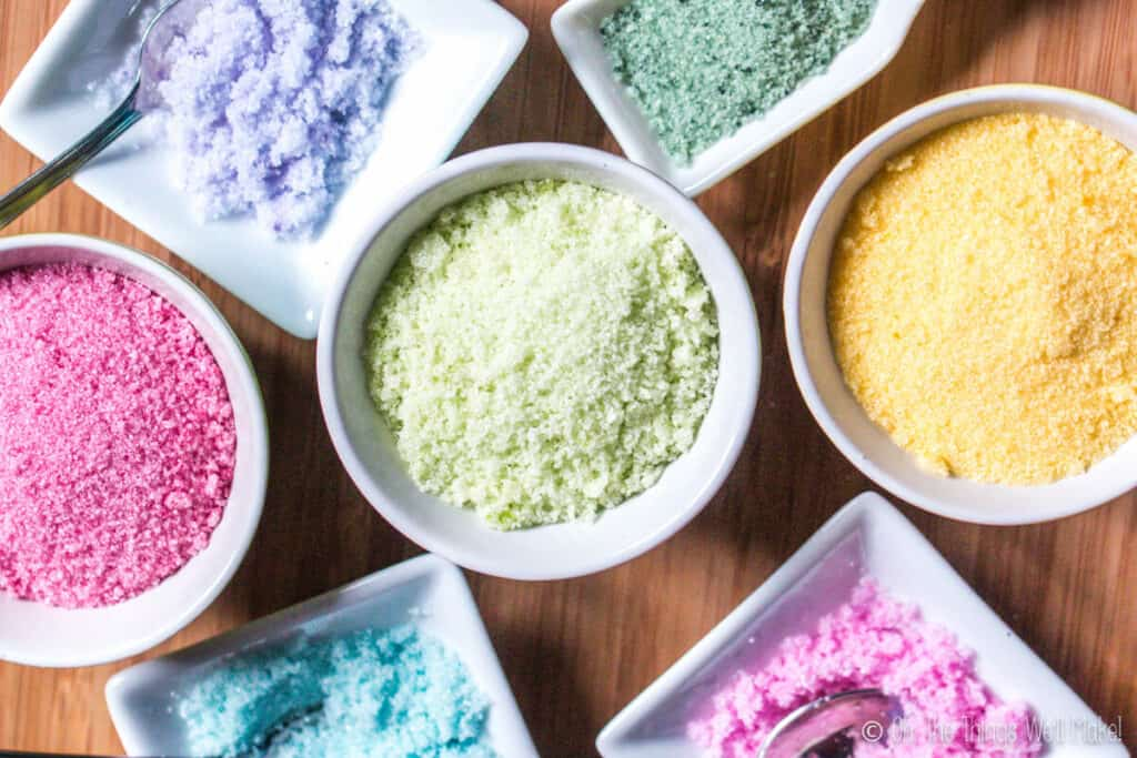 Overhead view of 7 small bowls filled with sugar that has been colored with a variety of homemade food colorings (in a variety of colors).