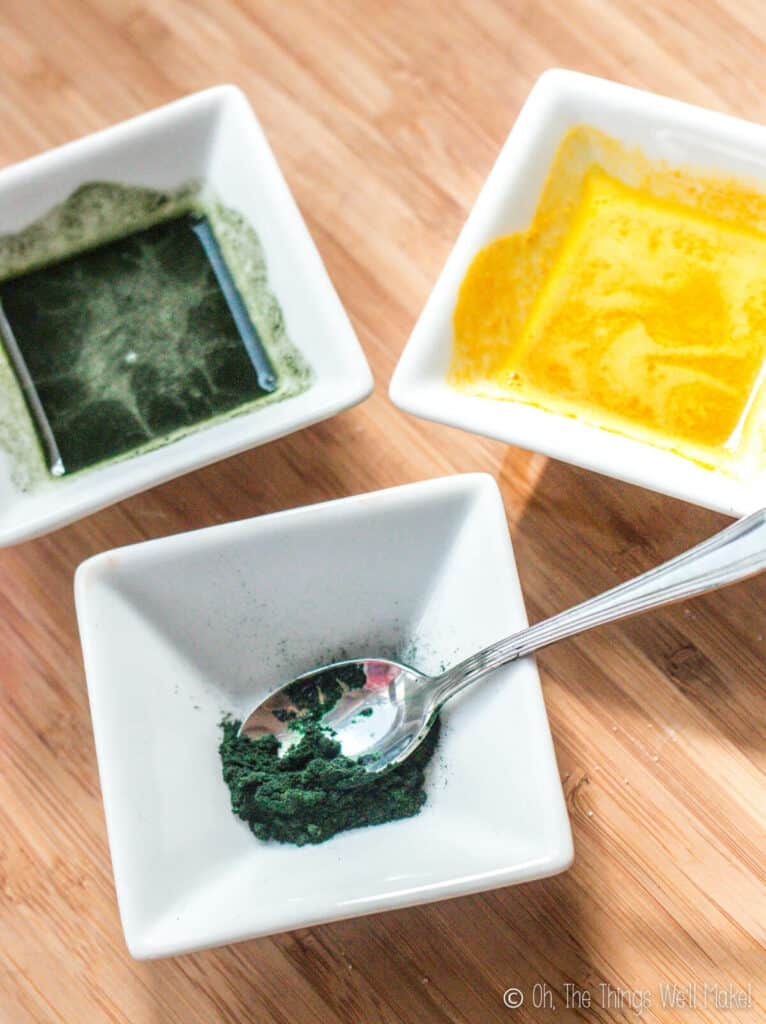 Overhead view of a small bowl with spirulina in front of 2 bowls, one with yellow coloring and another with green colorant