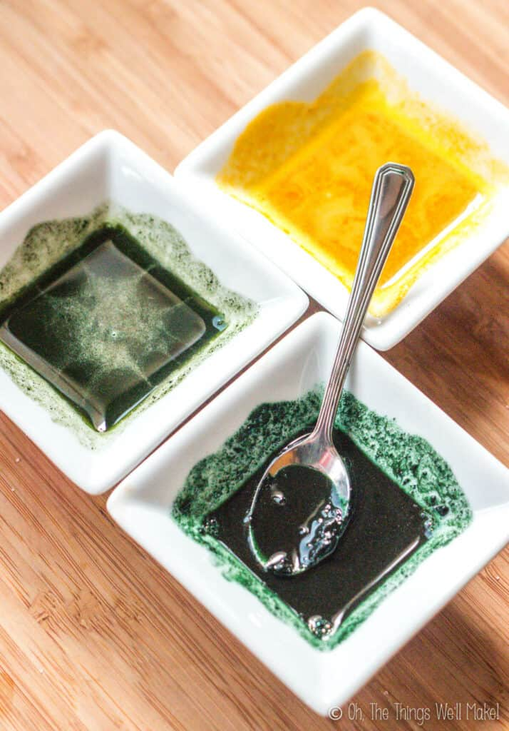 Overhead view of 2 green colorants and one yellow colorant in small white bowls
