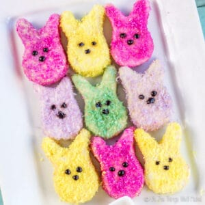 Closeup of 9 homemade marshmallow peeps shaped like bunnies and covered in brightly colored coconut sprinkles using natural colors.