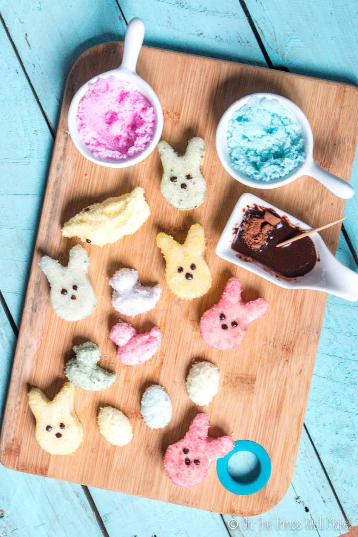 Overhead view of homemade marshmallow peeps covered with naturally colored sugar crystals on a bamboo cutting board.