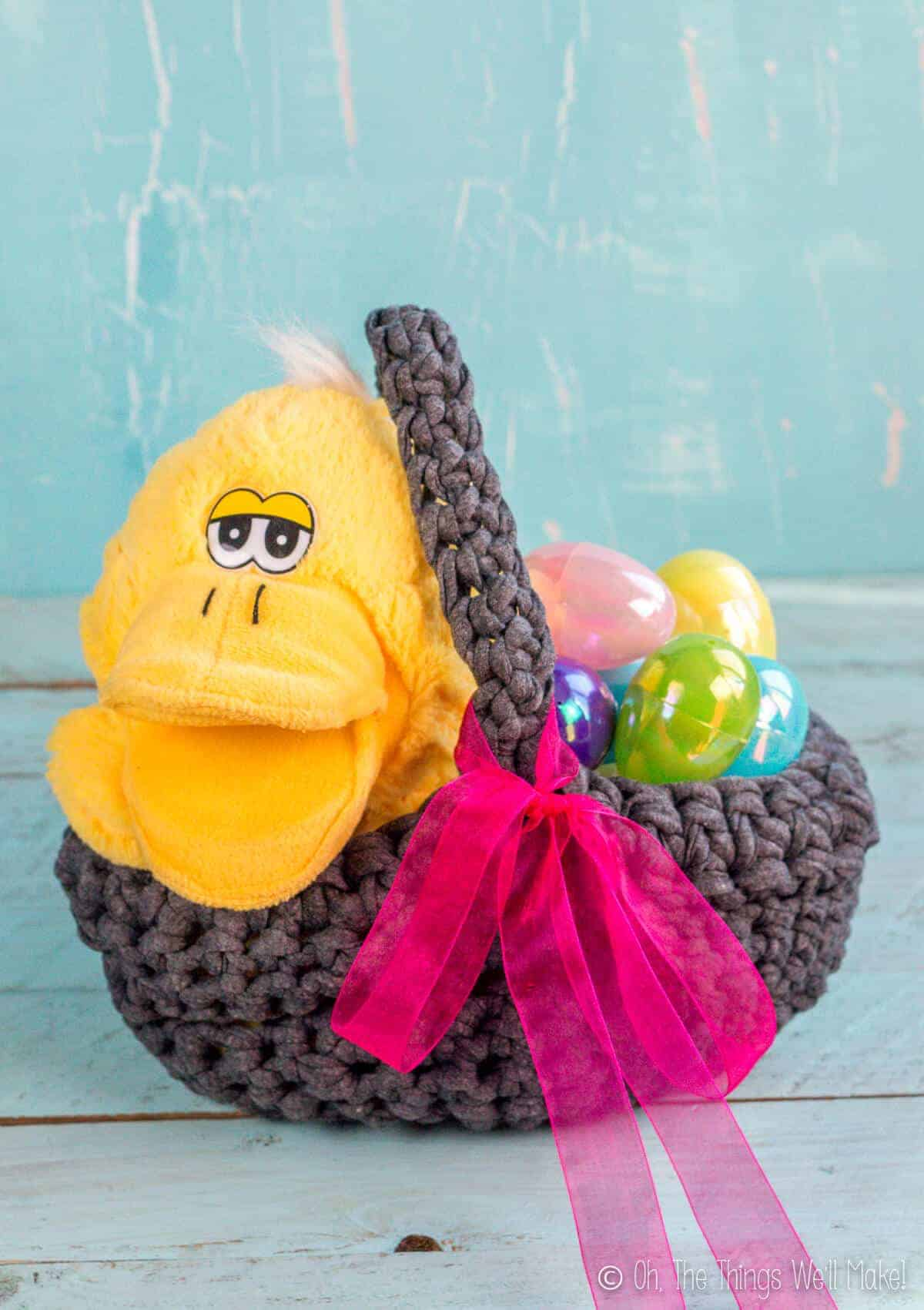 A homemade crochet Easter basket made from t-shirt yarn filled with a duck stuffed animal and plastic Easter eggs