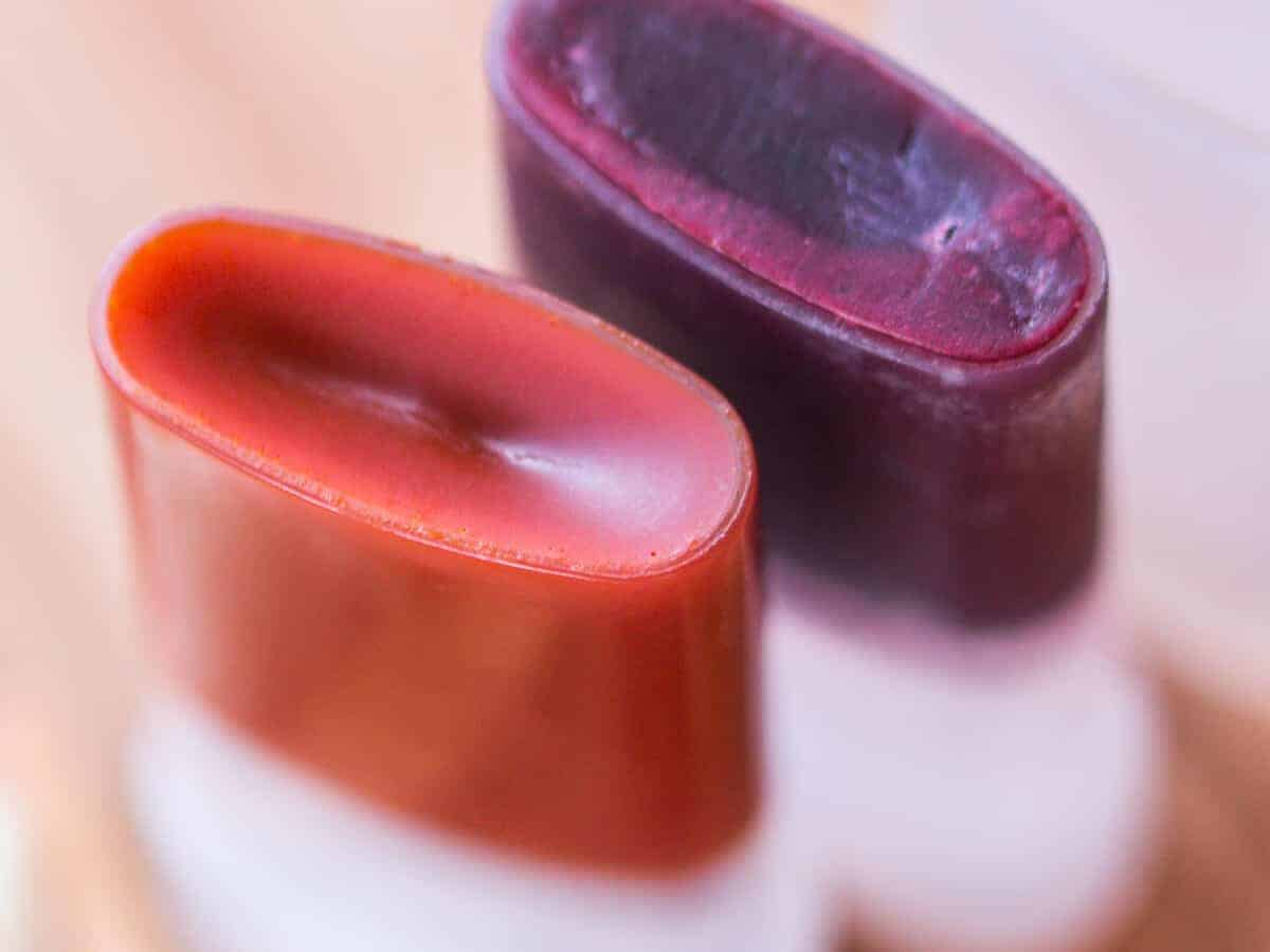 Overhead view of two homemade non comedogenic blush sticks. Red orange made out of annatto seeds and plum red made out of alkanet root powder.