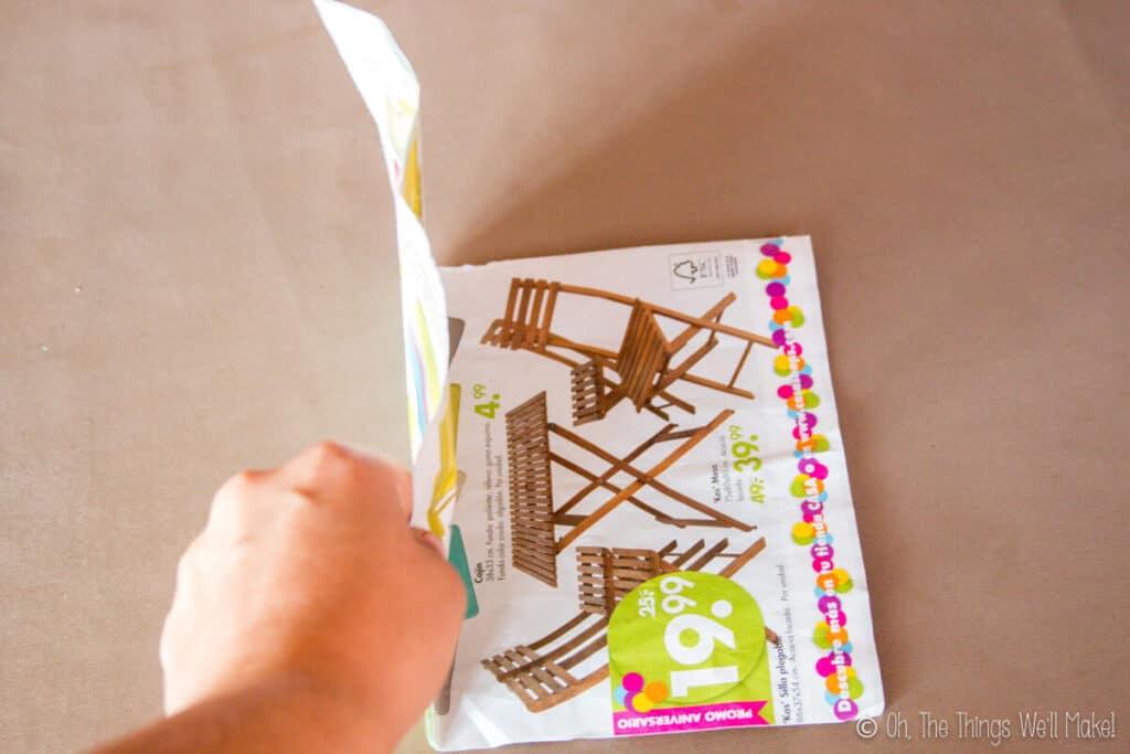 Folding a newspaper pamphlet in half.