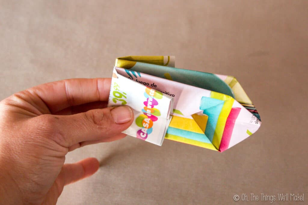 Holding a folded origami newspaper pot in the closed position.