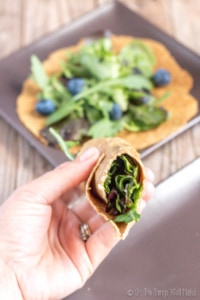 A salad wrapped in a flaxseed tortilla in front of with another tortilla and more lettuce on it.