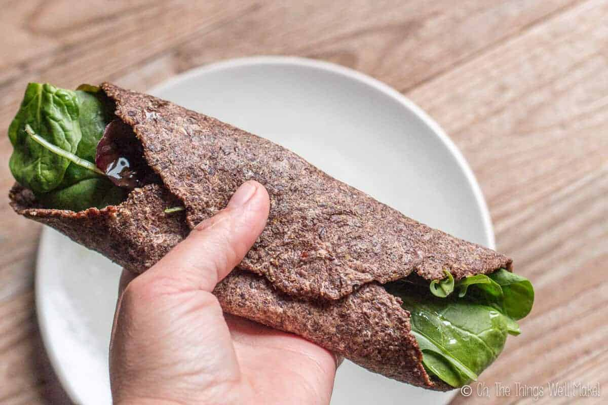 vegan paleo flaxseed tortilla made with brown flaxseeds shown rolled up around some lettuce.