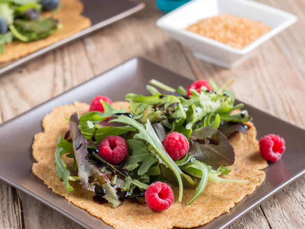 2 flaxseed tortillas on plates covered with lettuce and berries