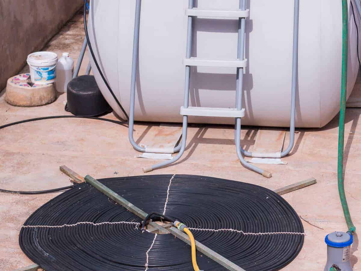 Homemade solar water heater made out of coiled black water hose laid on the ground next to a white water tank.