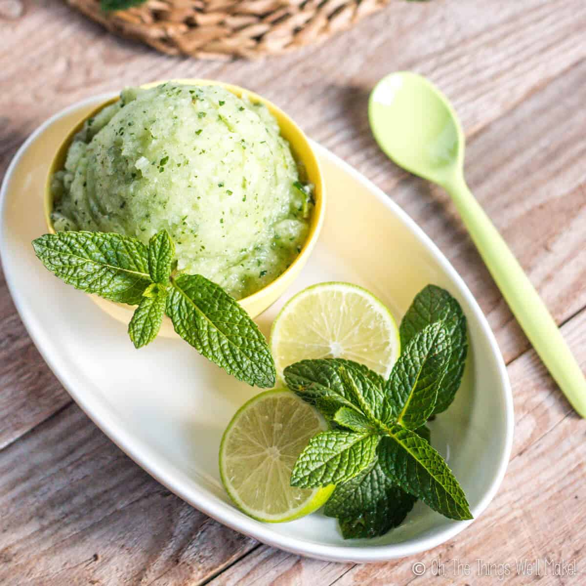 Overhead view of a mojito sorbet in a yellow bowl, garnished with spearmint and lime halves.