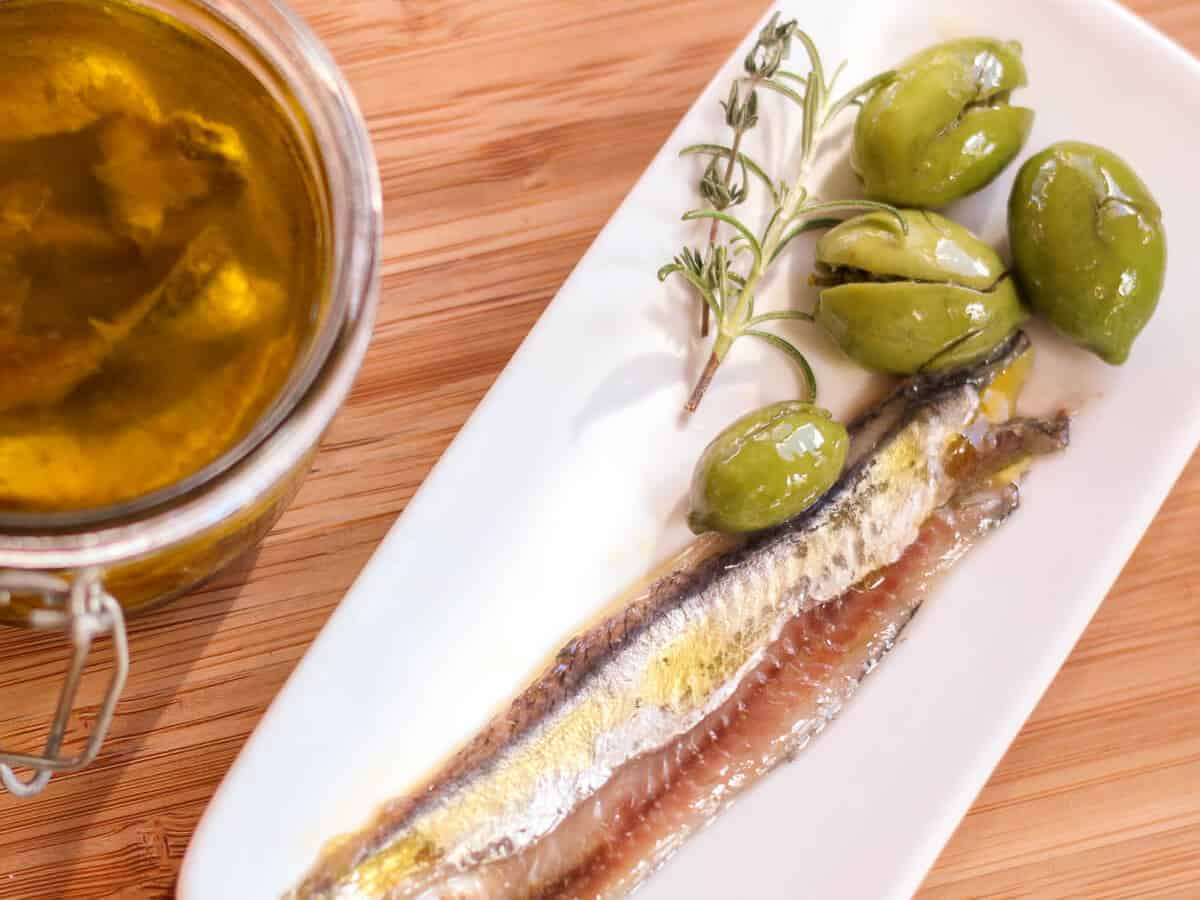Overhead view of a plate of homemade salt cured anchovy fillets with green olives on the side, next to a jar filled with anchovies covered in virgin olive oil and salt mixture.