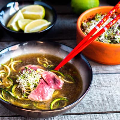A black bowl full of homemade Vietnamese pho made of beef broth, zucchini noodles, and slices of beef steak, with red chopsticks on the side. Bowls of lime and garnish are in the background.