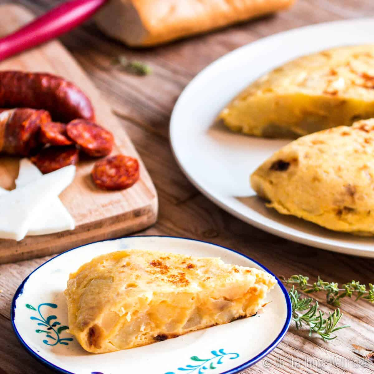 A slice of Spanish tortilla on a plate in front of some chorizo and cheese and the rest of the tortilla.