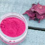 Overhead view of homemade beetroot powder in an open glass jar, next to some dried beetroot slices.