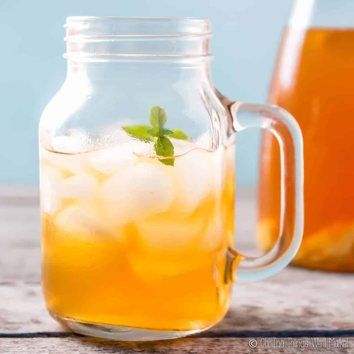 A mason jar mug filled with ice and a ginger switchel drink, garnished with a sprig of spearmint. There is a carafe of switchel in the background.