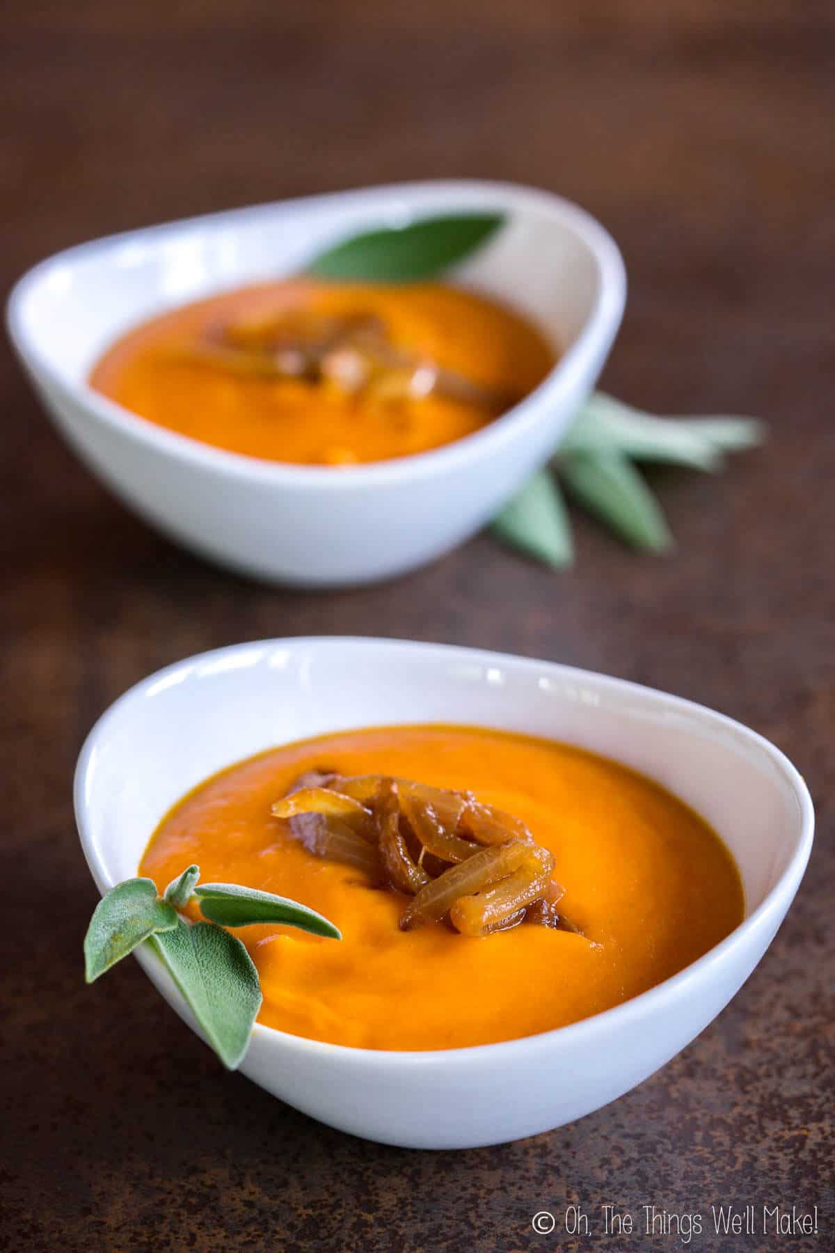Two bowls of creamy, roasted pumpkin soup garnished with caramelized onions and fresh sage leaves