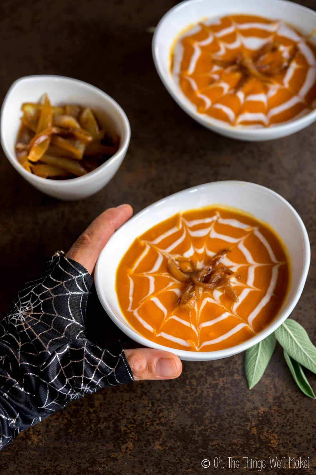 """A gloved hand reaching for a roasted pumpkin soup decorated for Halloween with a cream spiderweb and caramelized onion """"spiders."""""""