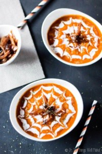 Overhead view of two bowls of a roasted pumpkin and red pepper soup decorated with green yogurt in a spiderweb design. They're garnished with caramelized onions, made to look like spiders on the web..
