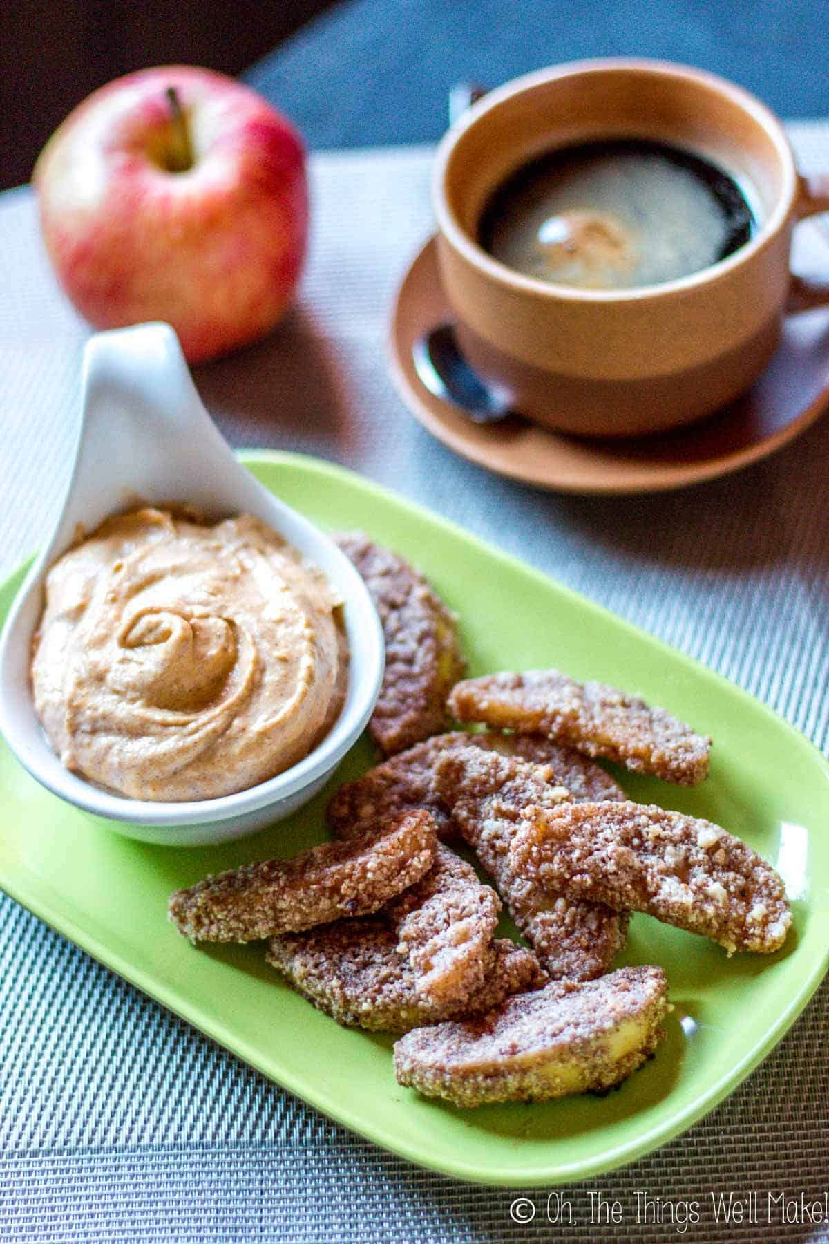 Paleo baked apple fries on a plate with pumpkin pie dip, served with coffee