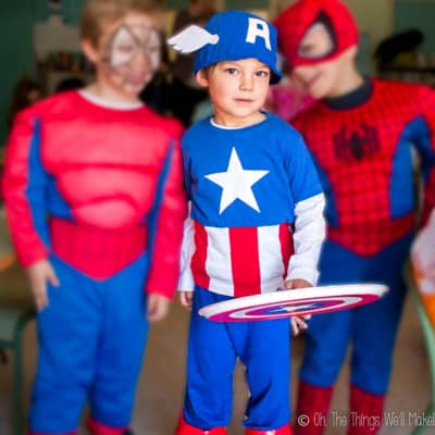 A young boy dressed in a vintage homemade Captain America costume with two friends dressed as spiderman (blurred out)