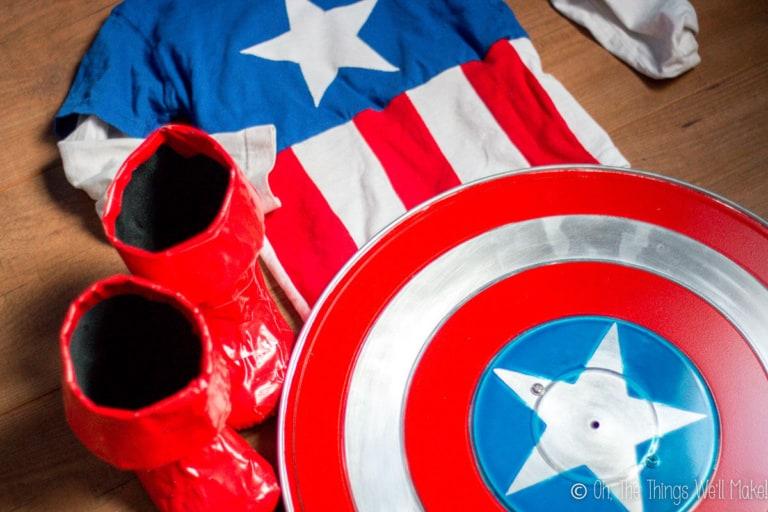 A homemade Captain America shield next to homemade boots and homemade costume